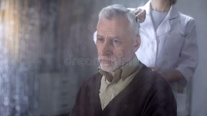 梳老人头发,护士的照料者照顾孤独的领抚恤金者在招待所 图库摄影