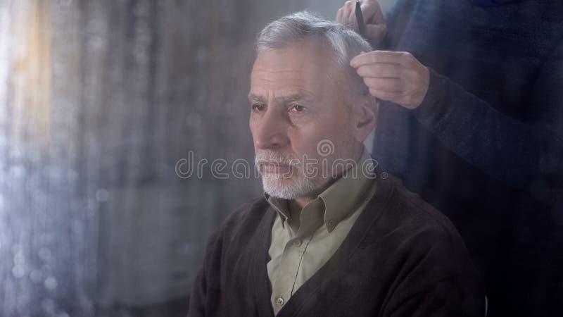 梳资深丈夫头发,晚年疾病补救,家庭支持的妇女 库存照片
