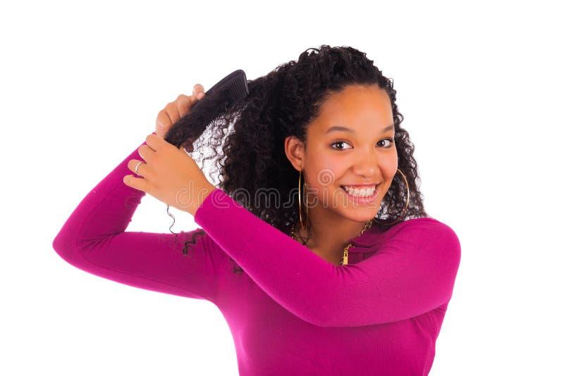 梳头发的年轻非裔美国人的妇女 免版税库存图片