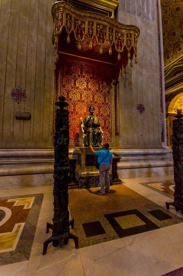 梵蒂冈,意大利- 2015年6月13日:传道者在圣伯多禄大教堂里面的圣伯多禄雕象在Vaticano 库存图片