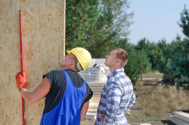 检查一个木墙板的建造者和工程师 免版税库存照片