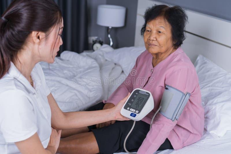 检查一名资深妇女的血压的女性护士 库存照片