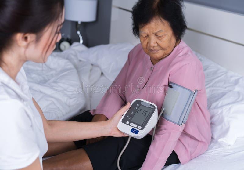 检查一名资深妇女的血压的女性护士 免版税库存图片