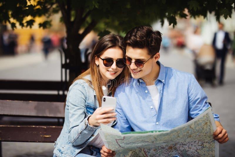 检查一张聪明的电话和纸地图的游人夫妇地点站立在街道上 旅行 免版税库存图片