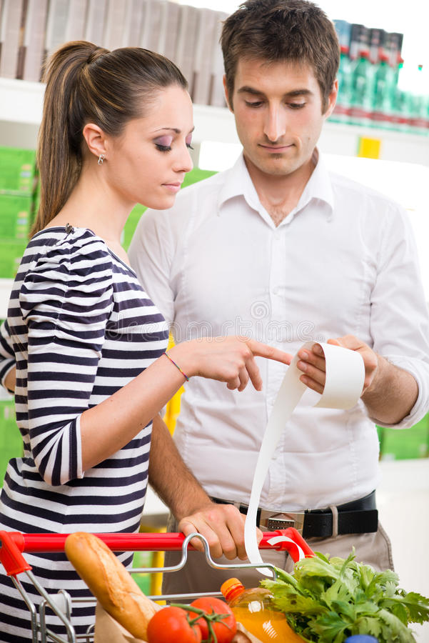 检查一张长的超级市场收据的夫妇 免版税库存照片