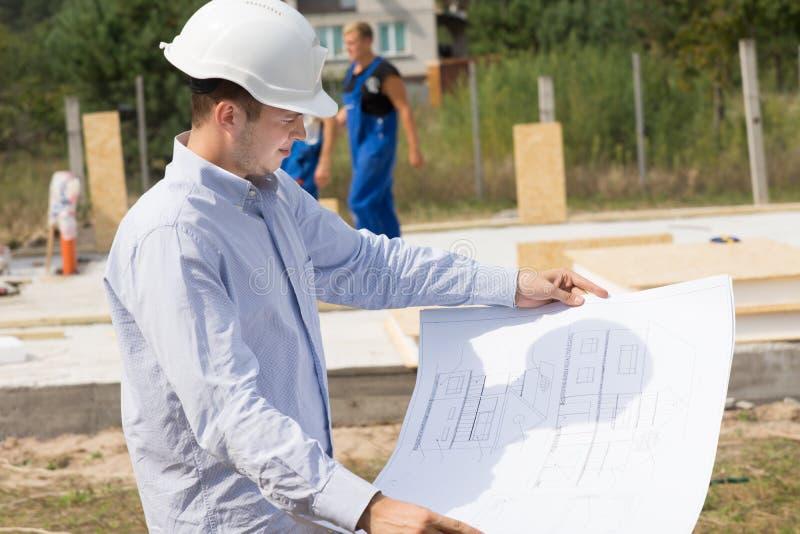 检查一张结构图的年轻建筑师 免版税图库摄影
