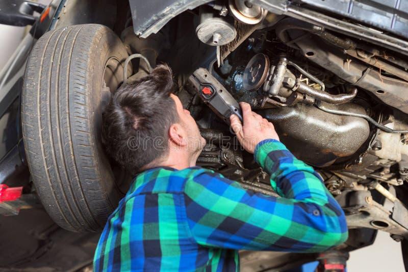 检查一辆被举的汽车的悬浮系统的英俊的汽车修理师在修理服务站 库存照片