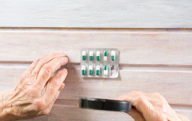 检查与放大镜的前辈药片 库存图片