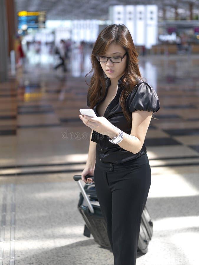 检查中国女孩的机场亚洲人她的电话 免版税库存照片