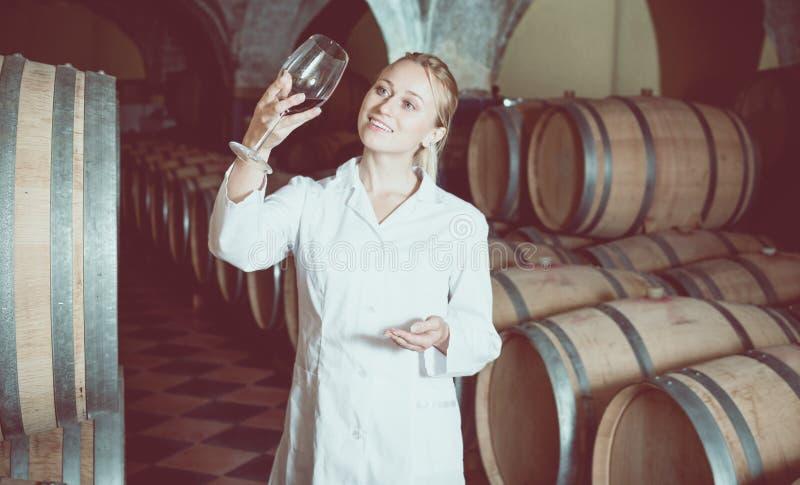 检查产品的质量的女性酒房子工作者 免版税库存照片