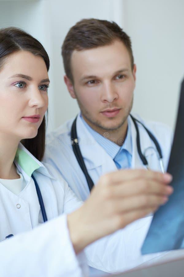 检查他们的患者X-射线和做诊断的两位年轻确信的医生 放射学家或创伤学专家 库存照片