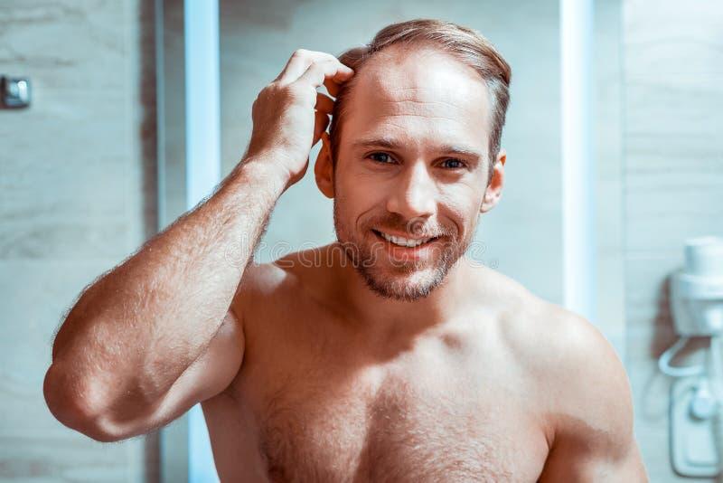 检查他的在镜子的英俊的赤裸人出现 免版税库存照片