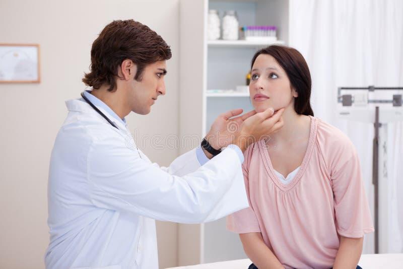 检查他的患者下颌的医生 免版税库存图片