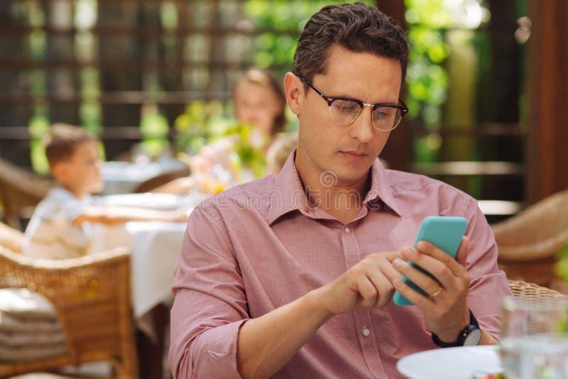 检查他的消息的繁忙的商人吃午餐 图库摄影