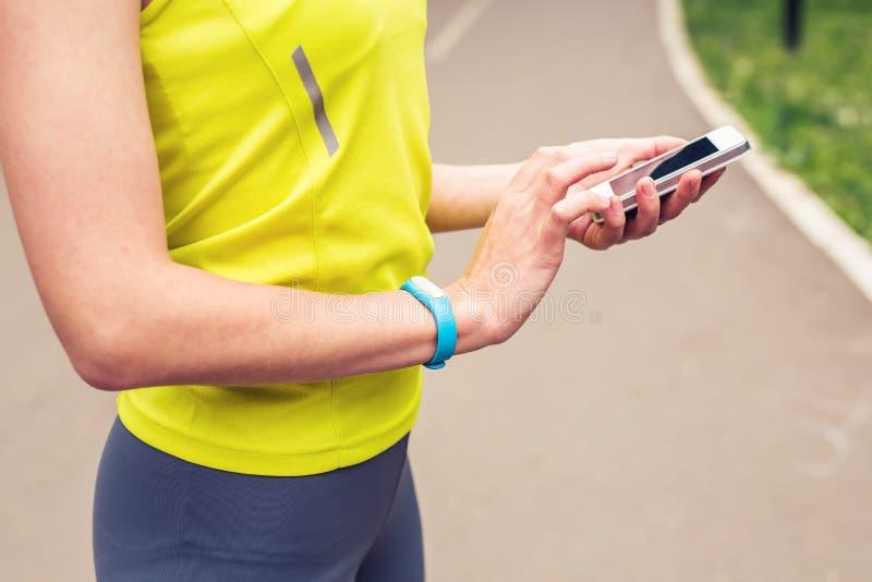 检查健身和健康的妇女跟踪便携的设备 免版税库存图片