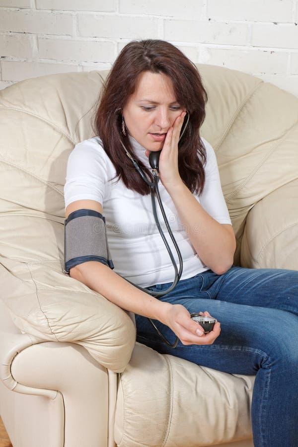 检查关心的女孩压的血液 免版税图库摄影