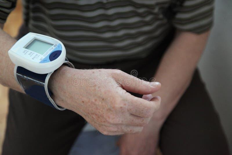 检查压的血液 在手边关闭血压monito的看法 在人的手上的数字式tonometr 测量她的血液前 库存照片