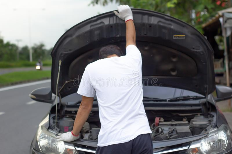 检查发动机油wh的技工佩带的手套开放汽车敞篷 免版税库存图片