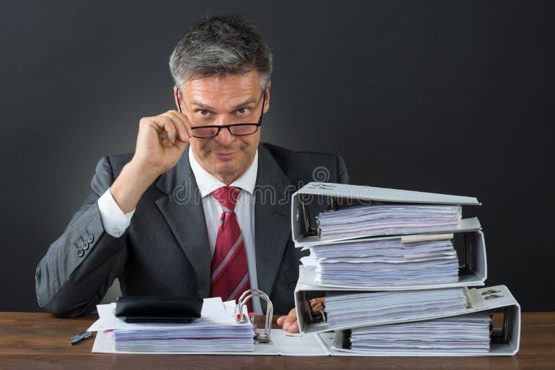 检查发货票的商人画象在书桌 免版税库存图片