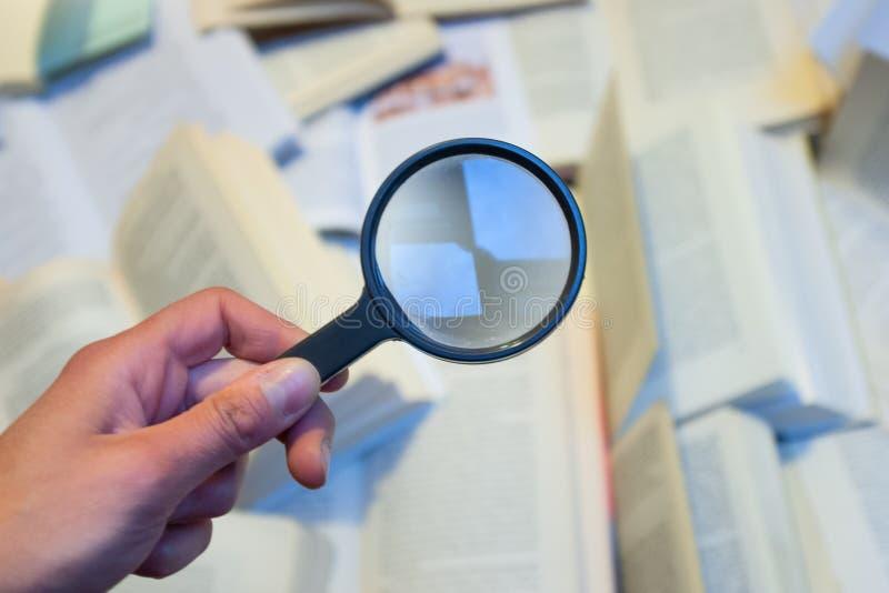 检查各种各样的书的放大镜 免版税库存图片