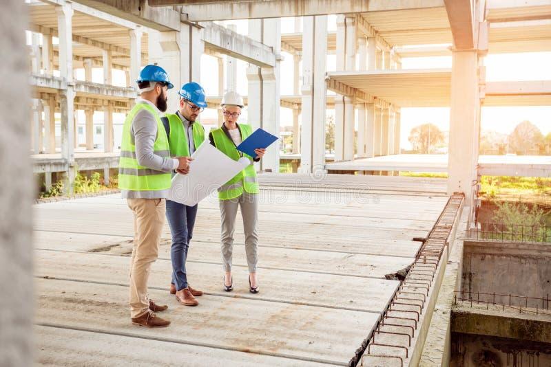 检查在一大工地工作的年轻工程师混杂的队工作进展 免版税库存图片
