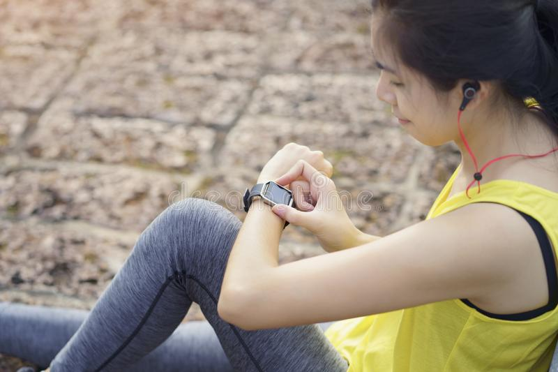 检查在巧妙的手表的妇女进展连接听音乐耳机,便携的健身设备 看心率的母赛跑者 库存图片