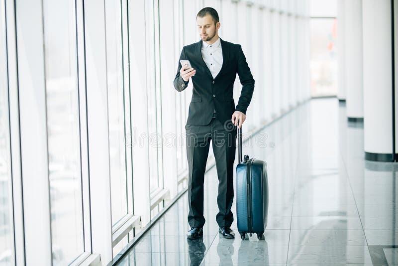 检查在手机的典雅的商人电子邮件,当走带着在机场终端里面时的手提箱 老练的男性雇主 免版税库存照片