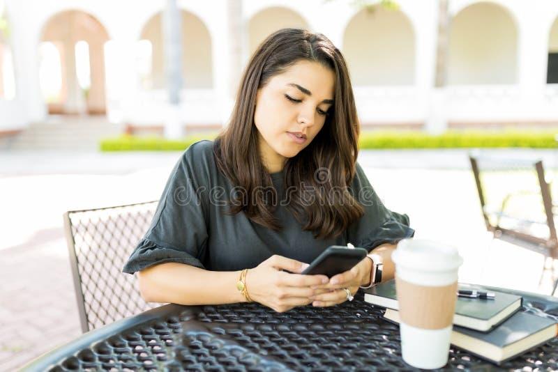 检查在智能手机的妇女电子邮件箱子在表上 免版税库存图片