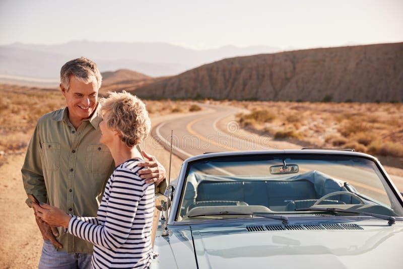 检查在智能手机的资深夫妇地图在沙漠路旁 库存照片