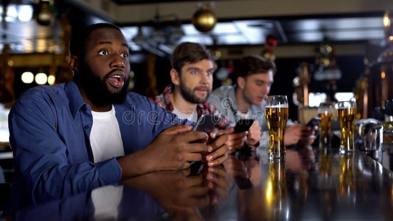 检查在智能手机,在酒吧,应用程序的观看的比赛的非裔美国人的人赌注 图库摄影