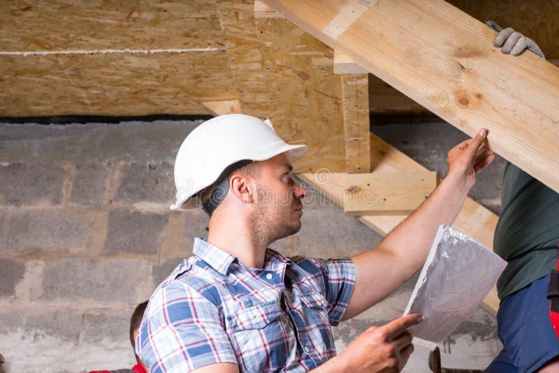 检查在楼梯的工头工作在新的家 免版税库存照片