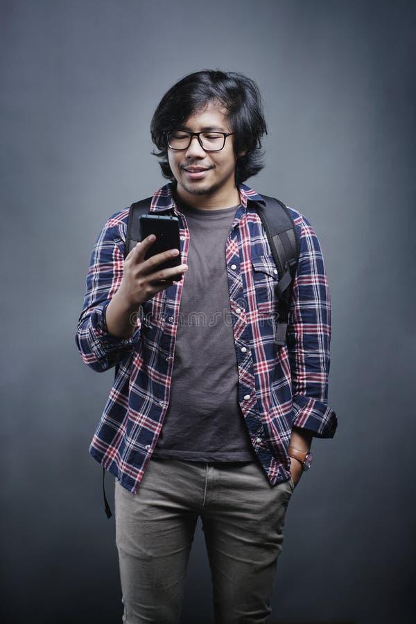 检查在灰色背景的亚裔大学生电话 库存照片