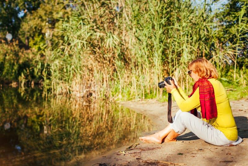 检查在照相机的中年妇女图象坐在秋天河岸之前 享受爱好的资深妇女 免版税库存照片
