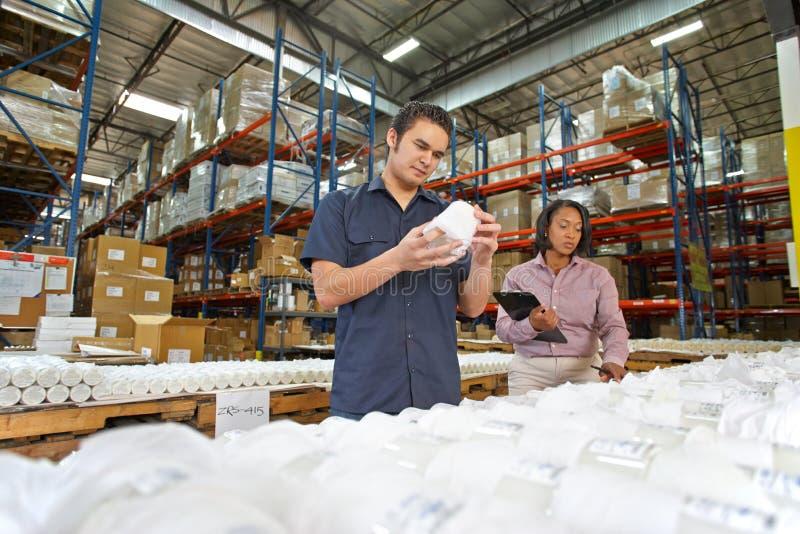 检查在生产线的工厂劳工和经理货物 免版税库存照片