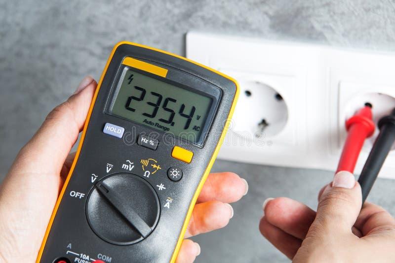 检查在电源插座的妇女电压 图库摄影