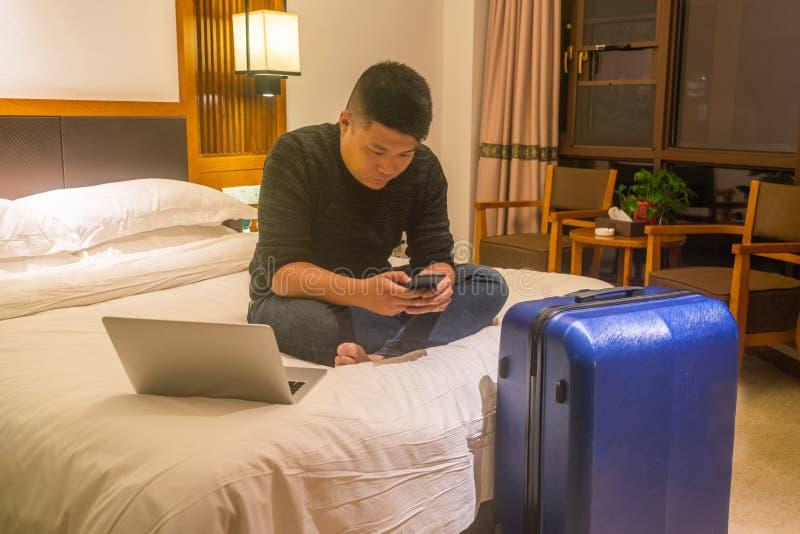 检查在电话的亚洲商人电子邮件在酒店房间 库存照片