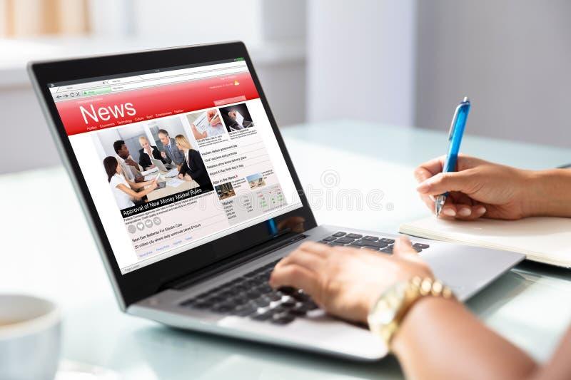 检查在膝上型计算机的女实业家网上新闻 免版税库存照片