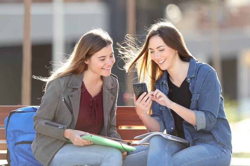 检查在长凳的愉快的学生智能手机 免版税图库摄影