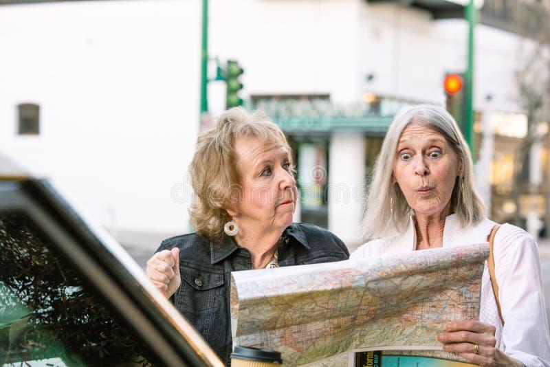 检查地图的两名迷茫的妇女 图库摄影