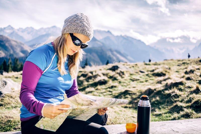 检查地图的妇女远足在山 免版税库存照片