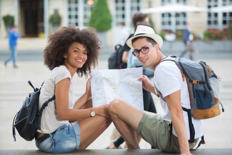 检查地图的年轻旅行的夫妇 免版税库存照片
