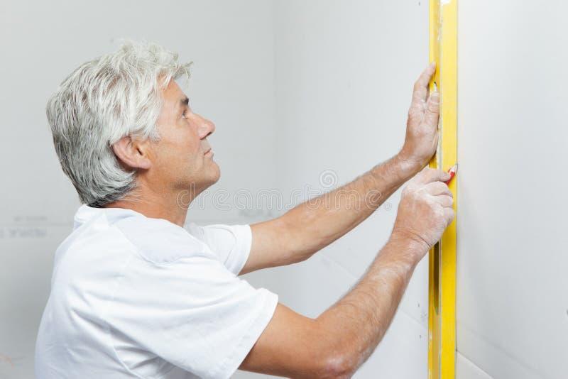 检查墙壁与水平仪 免版税库存图片