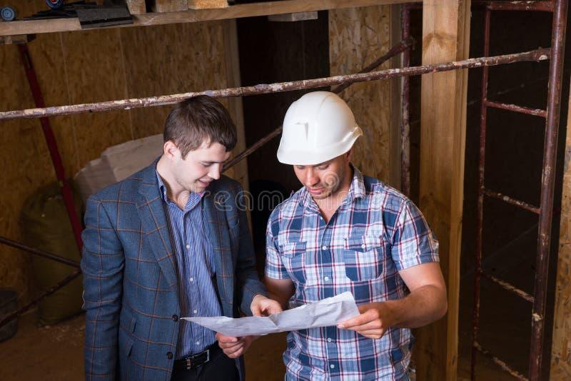 检查大厦计划的建筑师和工头 免版税库存照片