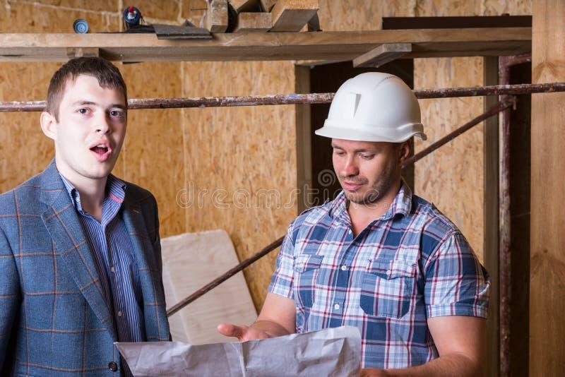 检查大厦计划的建筑师和工头 库存照片