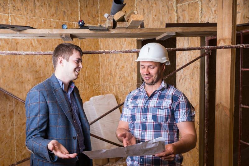 检查大厦计划的建筑师和工头 图库摄影