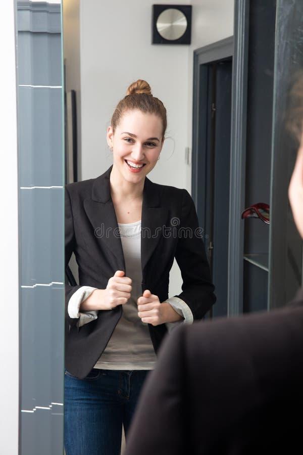 检查她成功的运作的衣服的笑的年轻美丽的女商人 免版税库存照片