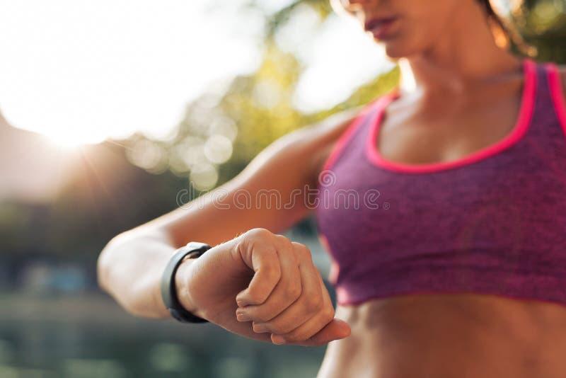 检查她的健身巧妙的手表设备的赛跑者 库存图片