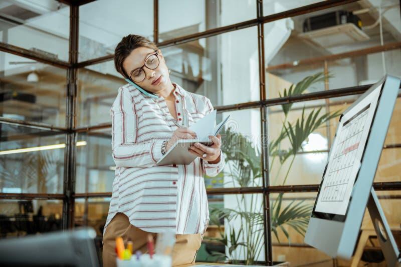 检查她的日程表的繁忙的女实业家,当安排会议时 免版税库存图片