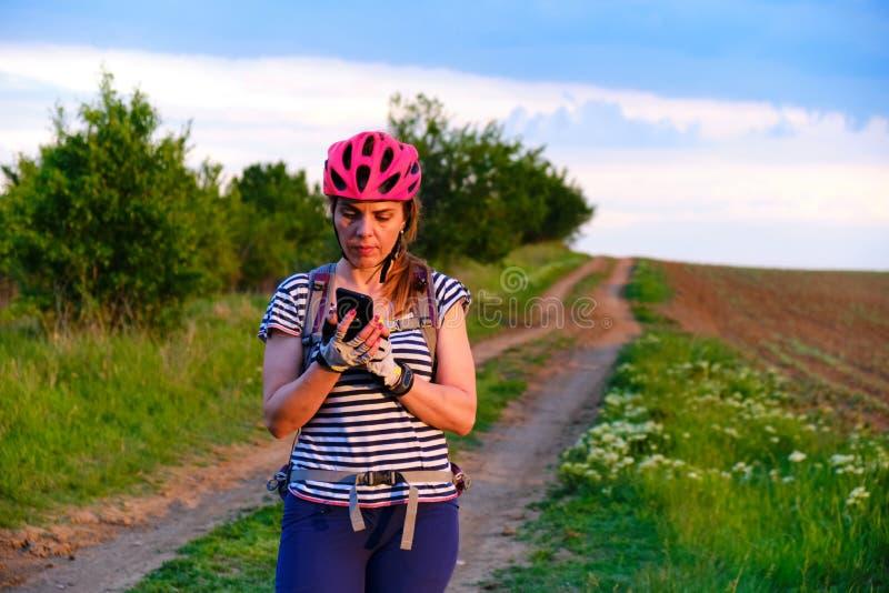 检查她的电话的女性骑自行车者在一条MTB路线的方向在乡下,在日落 免版税图库摄影