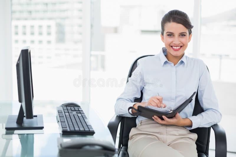 检查她的议程的喜悦的优等的棕色毛发的女实业家 免版税库存照片